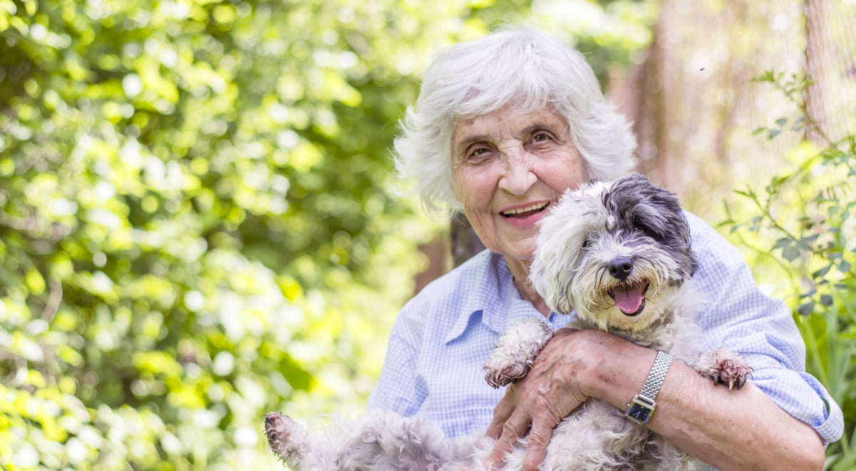 A woman and her dog enjoying the outdoors at Bridlewood Retirement Community