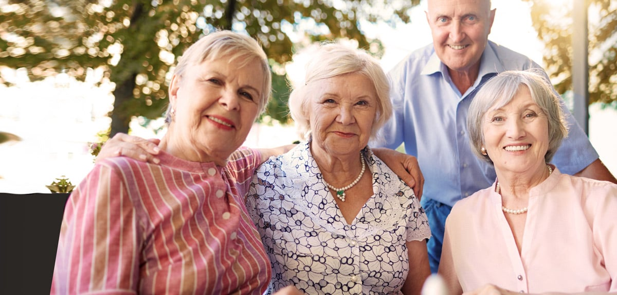 Four people smiling for the camera at Stirling Park Retirement Community
